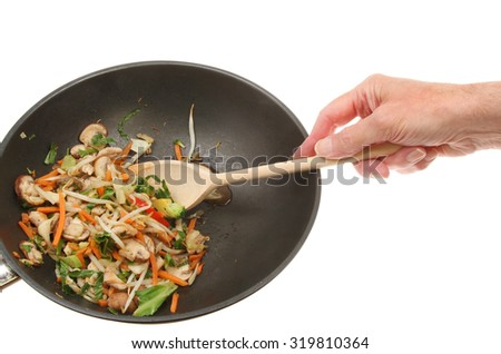 Hand with wooden spoon stirring chicken and stir fry vegetables in a wok against a white background - stock photo