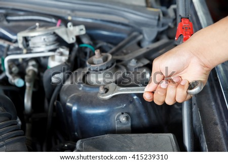 Hand with wrench checking car engine. - stock photo