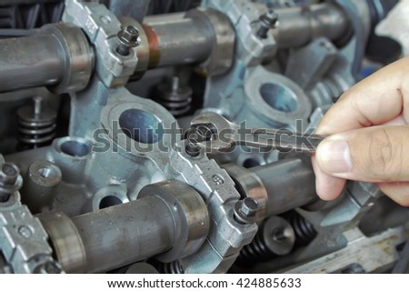 Hand with wrench checking car engine.