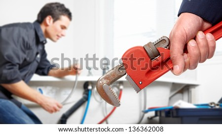 Hand with wrench. Plumber. Plumbing service concept. - stock photo