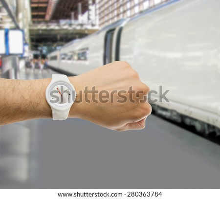 hand with wristwatch with train station in the background as the concept of punctuality in the transport - stock photo