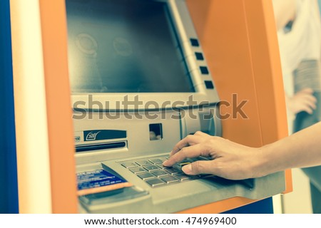 Hand withdrawing money from ATM machine. Vintage filter