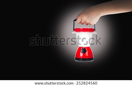 Hand woman holding plastic electric lantern with lit flame in darkness, concepts of searching and direction - stock photo