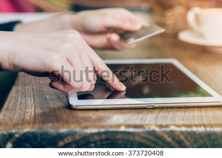 hand woman pays by credit card for online purchase on a tablet computer. - stock photo