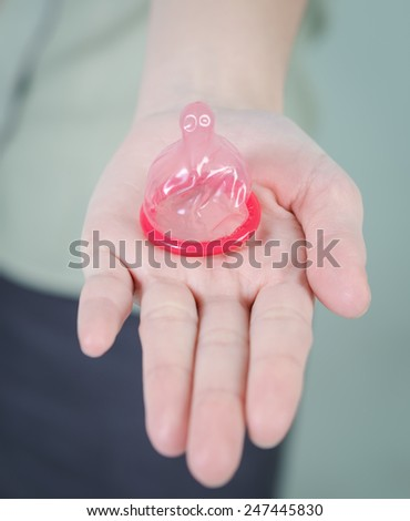 hand woman showing a condom , Focus on the condom in the foreground - stock photo
