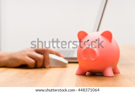 hand working with computer, piggy bank, saving money concept