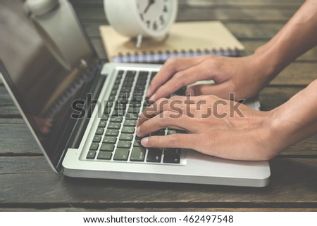 hand working with laptop on wooden background