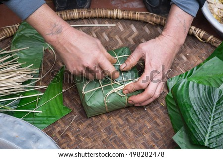 Hand wrapping Chung Cake in square shape with long node string split from bamboo. It is wrapped as tight as possible to keep cake from mold or spoiled. Traditional Vietnamese New Year (Tet) food.