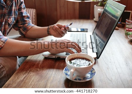 hand write note on paper with hold credit card with laptop,hands holding credit card and using laptop shopping online,personal loans,businessman hand busy using laptop at office desk,online lifestyle  - stock photo