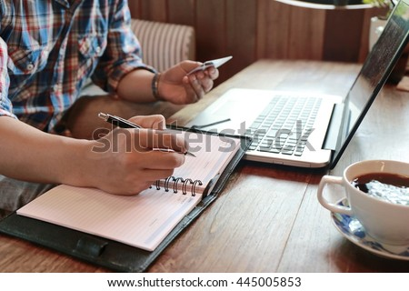 hand write note on paper with hold credit card with laptop,hands holding credit card and using laptop shopping online,personal loans,businessman hand busy using laptop at office desk,online lifestyle