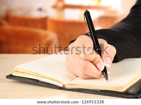 Hand write on notebook, on bright background - stock photo