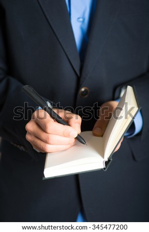 Hand writes in a notebook. advertising or business concept, isolated on a gray background.