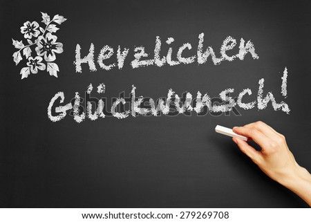 "Hand writes in German ""Herzlichen Glueckwunsch!"" (Congratulations) on blackboard - stock photo"