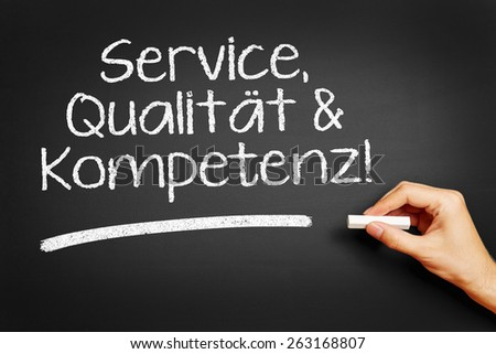 "Hand writes in German ""Service, Qualitaet & Kompetenz!"" (Service, quality & competence!) on blackboard"