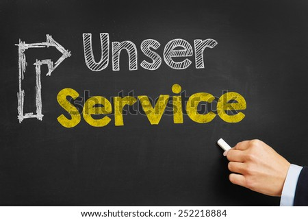 "Hand writes in German ""Unser Service"" (our service) with arrow on blackboard"
