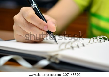 Hand writes on a book with a pen (Selective focus) - Business or education note - stock photo