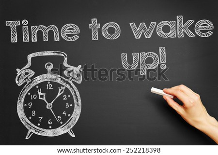 "Hand writes ""Time to wake up!"" on blackboard"