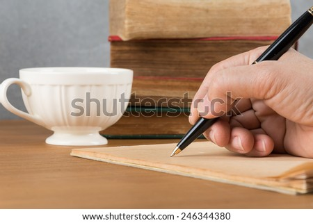 Hand writing a notebook on table - stock photo