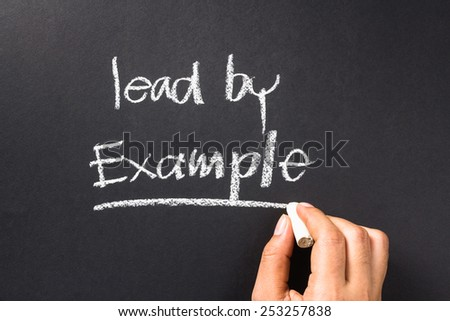 Hand writing a phrase Lead By Example on chalkboard