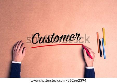 Hand writing a single word Customer on paper - stock photo