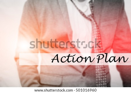 Hand writing Action Plan with the young business man on background. Business concept. Stock Photo.