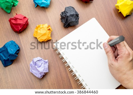 Hand writing at open blank ring binder white book and pencil with group of colorful crumpled paper ball on dark brown table top, Business Brainstorming concept,mock up for adding your text - stock photo