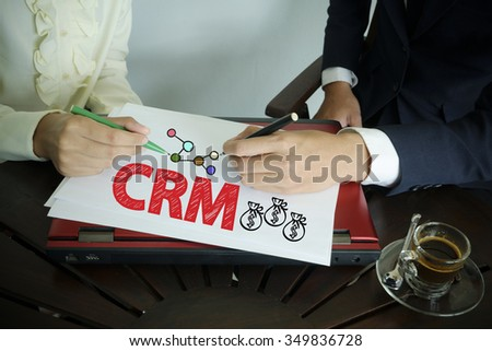 hand writing CRM text with two business person ,team work concept - stock photo