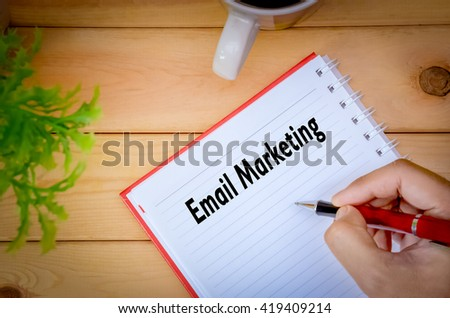 Hand writing Email Marketing on book surrounding by coffee cup and green plant on wooden background.