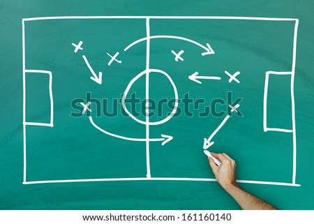 Hand writing football game strategy on green blackboard - stock photo
