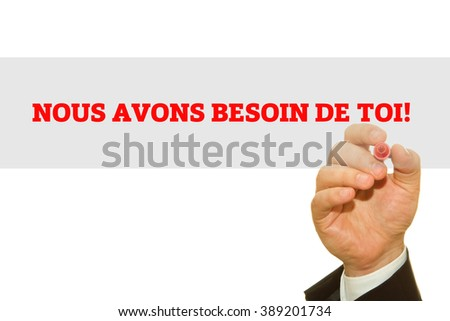Hand writing French Slogan NOUS AVONS BESOIN DE TOI! (We Need You!) on a transparent wipe board.