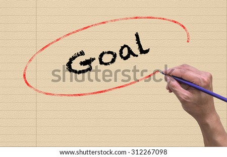 Hand writing Goal by pencil on paper Notebook background. Business and Education concept