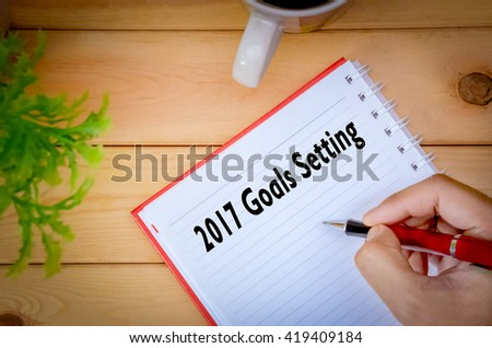 Hand writing 2017 Goals Setting on book surrounding by coffee cup and green plant on wooden background.