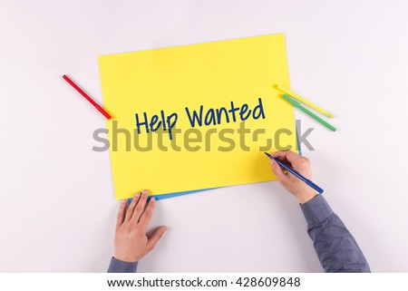 Hand writing Help Wanted on yellow paper - stock photo