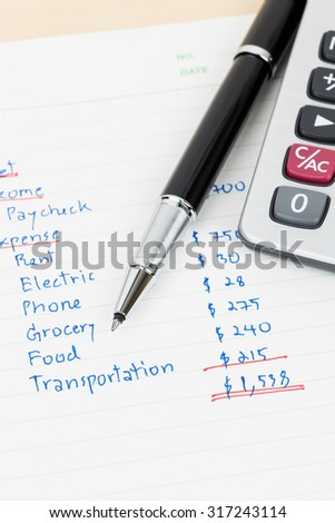 Hand writing home budget with calculator - stock photo