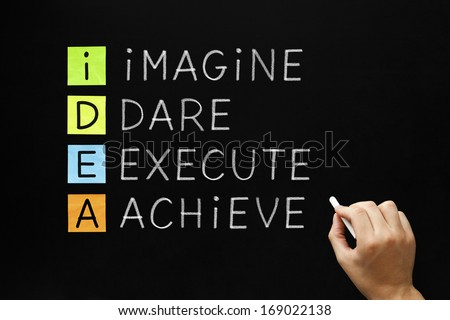 Hand writing IDEA - Imagine Dare Execute Achieve with white chalk on blackboard. - stock photo