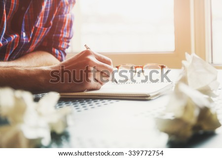 hand writing in notebook with pen and paper balls - stock photo