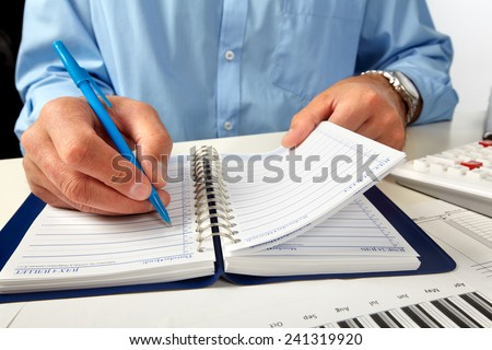 Hand writing in notepad. Businessman working in office - stock photo