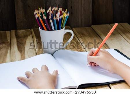 Hand writing in open notebook on table - stock photo