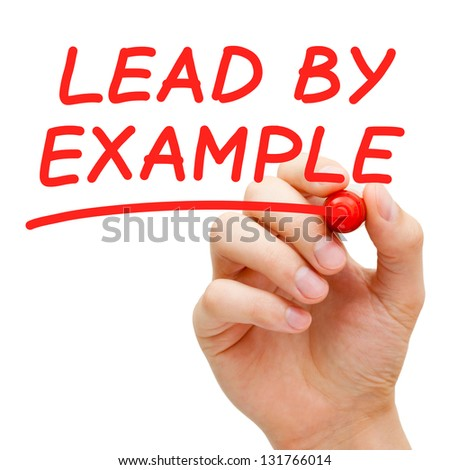 Hand writing Lead By Example with red marker on transparent wipe board. - stock photo