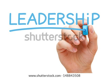 Hand writing Leadership with blue marker on transparent wipe board.