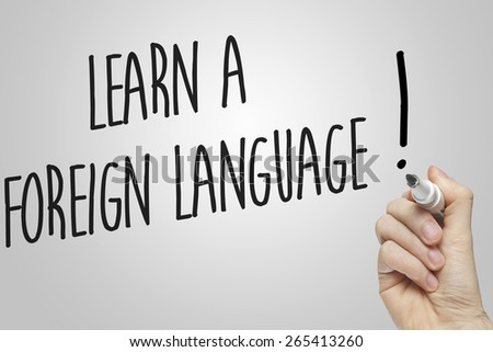 Hand writing learn a foreign language on grey background - stock photo