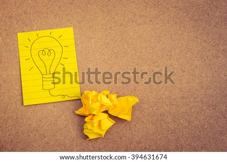 Hand writing light bulb on yellow paper on brown background with crumpled paper ball - business concept idea and strategy - stock photo