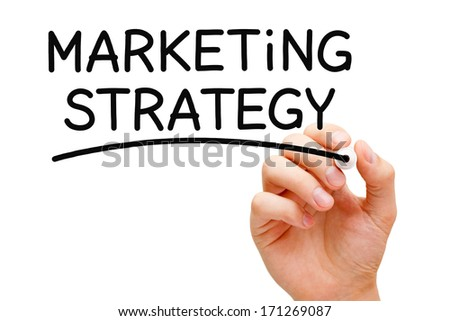 Hand writing Marketing Strategy with black marker on transparent wipe board.