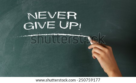 Hand writing Never Give Up! - Motivation Concept on a blackboard