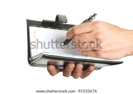 hand writing notes into a personal organizer isolated on white background - stock photo