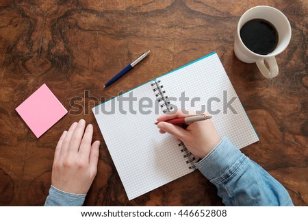 hand writing on a copy book on wooden table - stock photo