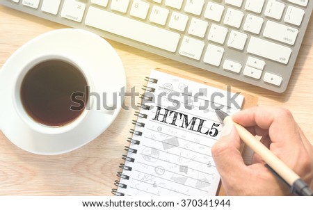 Hand writing on book message HTML5. A keyboard and a glass coffee table.Vintage tone. - stock photo