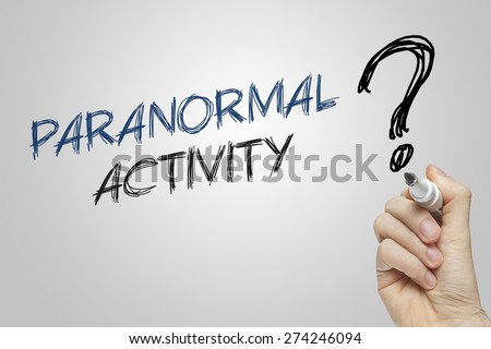 Hand writing paranormal activity on grey background - stock photo
