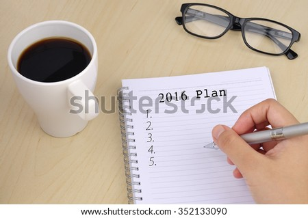"""Hand Writing """"2016 Plan"""" on Notebook with Cup of Coffee and Spectacle On Wooden Table - stock photo"""