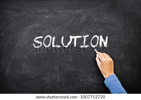"Hand writing ""SOLUTION"" on blackboard."